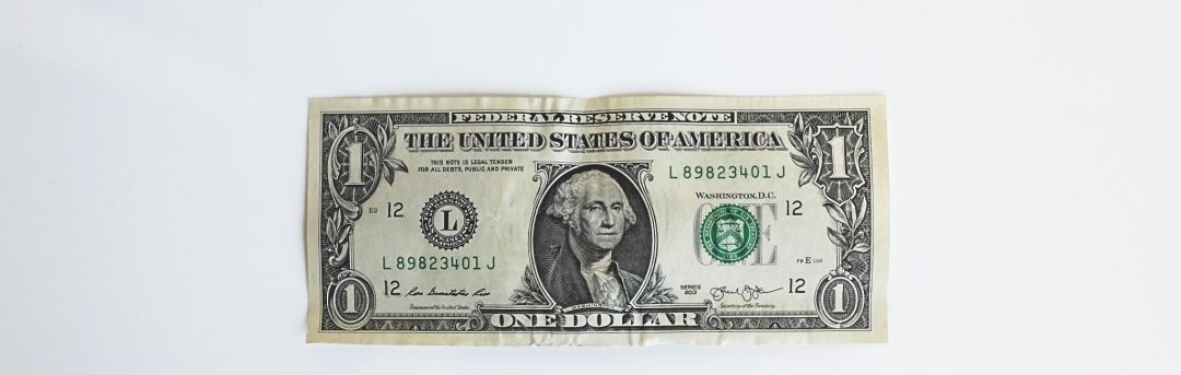 A single dollar bill, slightly crumpled but still straight, lays face up on a white surface.