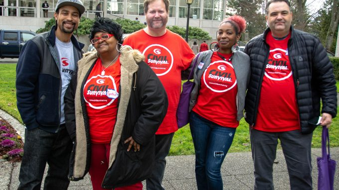 "5 people stand in a row, posing for the camera together. They are all smiling and wearing red shirts that say ""civil survival"" on them"