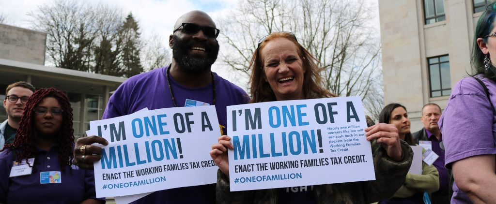 "Two people stand facing the camera. They are smiling and laughing and are holding signs that say ""I'm One of a Million!"""