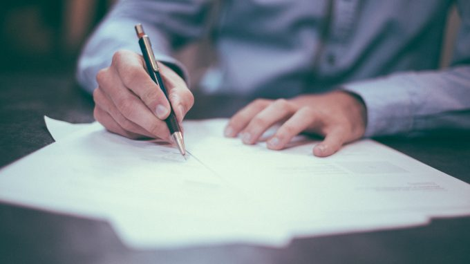 A person sits at a table writing on several pieces of paper, perhaps filling out forms. You can only see the person's hands, the pen they are holding, and part of the blue shirt they are wearing. The whole photo is slightly blurred out.