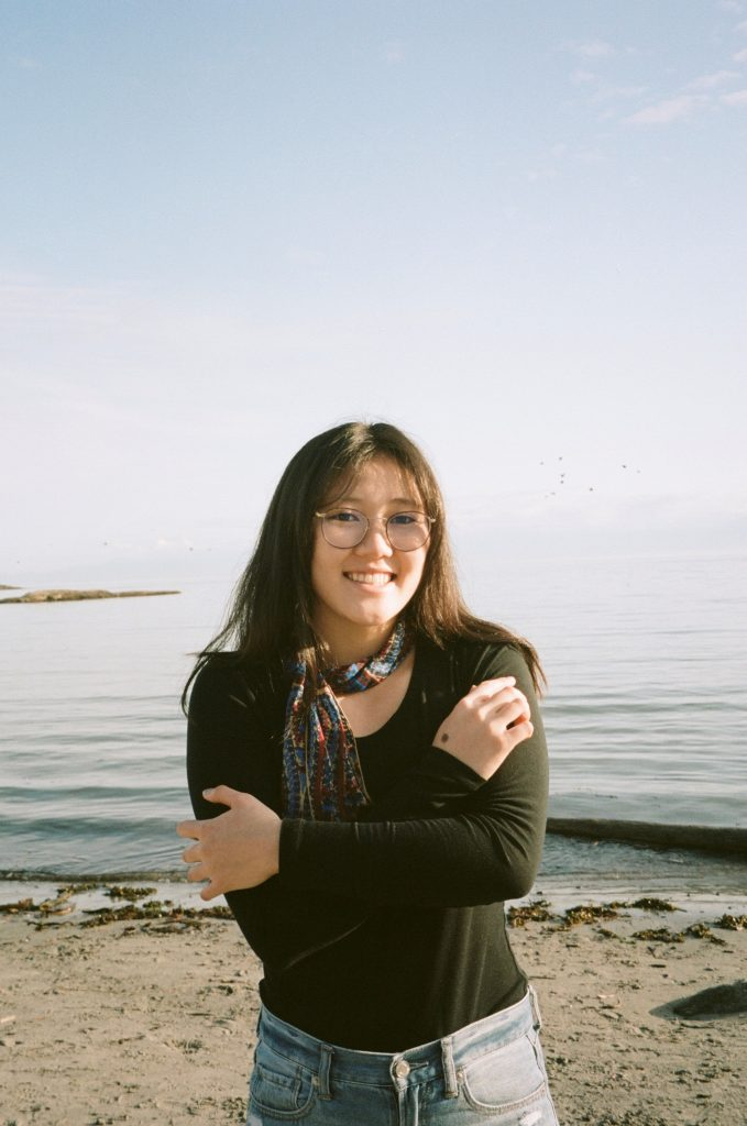 Woman in black shirt standing on a beach, with the ocean horizon behind her. Her arms are crossed and she is wearing glasses.