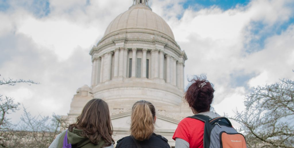 3 people with backs turned facing the Washington State Capitol building